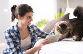 picture of caress  - Smiling woman with tablet and beautiful cat in the living room.