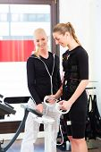 foto of contactor  - Female coach controlling results after ems electro muscular stimulation training with body fat measuring - JPG