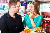 picture of diners  - Friends or couple eating fast food with burger and fries in American fast food diner - JPG