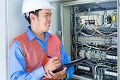 picture of breaker  - Asian Indonesian Technician or electrician making function test on breaker box or switchbox with power lines on construction site or in factory for acceptance - JPG