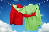 stock photo of button down shirt  - Laundry hanging on a clothesline concept for love and romance with two shirts embracing each other looking at a blue sky - JPG