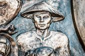 image of metal sculpture  - Part of bronze monument with asian man in traditional conical hat - JPG