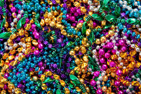 picture of mardi-gras  - A background of colorful mardi gras beads including gold blue green pink and purple - JPG