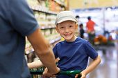 pic of grocery cart  - positive smiling boy sitting in the shopping cart while grocery shopping with his father together at supermarket  - JPG