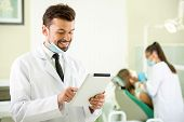 foto of dentist  - Smiling dentist with a tablet in hands - JPG