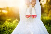 stock photo of life event  - Photograph of a unrecognizable bride holding wedding shoes with red hearts - JPG
