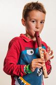 stock photo of flute  - a child playing on a flute on wood - JPG