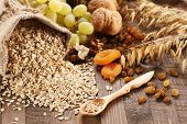 picture of oats  - oatmeal in a sac ears of oats dried apricots raisins grapes nuts on the background of wooden planks and sacking - JPG