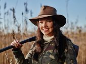 image of shotgun  - Waterfowl hunting smiling female hunter carry a shotgun and she looks toward the camera reeds and blue sky on background - JPG
