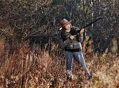 stock photo of shotgun  - Waterfowl hunting the female hunter use the shotgun autumnal bushes on background - JPG