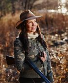 foto of shotgun  - Waterfowl hunting the female hunter carry a shotgun autumnal bushes on background - JPG