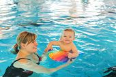 foto of swimming  - Little baby boy and his mother learning to swim in an indoor swimming pool - JPG