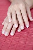 foto of french manicure  - closeup of hands of a young woman with the french manicure on a red mat on her wedding day  - JPG