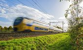 picture of high-speed train  - Passenger train moving at high speed in sunlight  - JPG