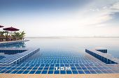 foto of infinity pool  - The edge of an infinity swimming pool at a tropical hotel on the edge of a river  - JPG