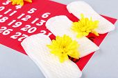 image of menses  - Sanitary pads and yellow flowers on light grey background - JPG