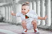 stock photo of little angel  - Little boy with angel wings on old city background - JPG