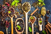 picture of black tea  - Virious kinds of tea in wooden spoons on black table - JPG
