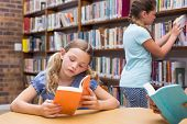 stock photo of pupils  - Cute pupils reading in library at the elementary school - JPG