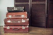 pic of yesteryear  - Old suitcases on a background of dark wood screen - JPG