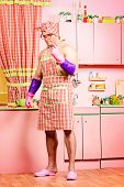stock photo of apron  - Serious muscular man in an apron standing in the pink kitchen - JPG