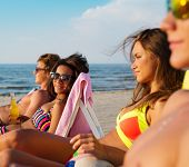 image of sunbathers  - Group of multi ethnic friends sunbathing on a deck chairs on a beach  - JPG