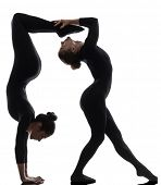 stock photo of contortionist  - two women contortionist practicing gymnastic yoga in silhouette on white background - JPG