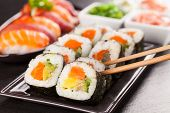picture of sushi  - Delicious sushi rolls served on black plate and stone - JPG