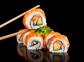 pic of chopsticks  - Delicious sushi rolls served on black table with chopsticks - JPG