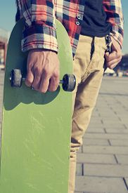 picture of swagger  - a young man with a plaid shirt holding a green skateboard in his hand - JPG