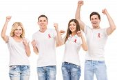 stock photo of hiv  - Group of young positive people with red ribbon supporting AIDS HIV prevention - JPG
