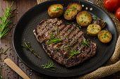 foto of ribs  - Beef rib eye steak with rustic potatoes fresh herbs and tomatoes sprinkled sea salt and herbs - JPG