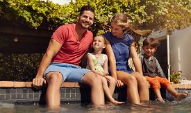 picture of hot couple  - Outdoor shot of beautiful young family sitting next to swimming pool with their feet in water - JPG