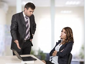 stock photo of inappropriate  - Female office employee caught by manager at inappropriate social networking during working hours Boss is criticising her pointing the laptop - JPG
