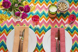 stock photo of chevron  - Overhead Bright colorful table setting with multi colored chevron pattern tablecoth - JPG