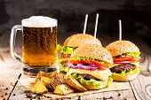 homemade burgers with beef and fried potatoes and glass of cold beer on wooden table on a dark backg poster