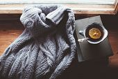 Warm and comfy autumn or winter concept. Book, cup of lemon tea and sweater on wooden window sill in poster