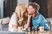 Affectionate Romantic Couple Kissing At Table In Cafe poster