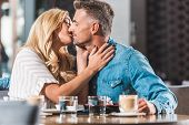 Affectionate Boyfriend And Girlfriend Kissing At Table In Cafe poster