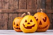 Traditional Halloween Pumpkins On Wooden Background. Funny And Scary Faces Of Pumpkins For Halloween poster