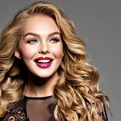 Blond smiling woman with long curly beautiful hair. Makeup. Fashion make-up.  Closeup portrait. Gorg poster