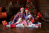 A Big Family In Front Of The Fur-tree And Fireplace With Gifts. New Years Eve. Love, Family And Hap poster