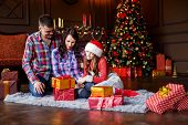 Mother Father And Daughter Near The Christmas Tree. Love, Family And Happiness Consept. New Years E poster
