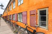 Many Bicycles Stands At Color Historical Building In Traditional Style Of Copenhagen, Denmark. Old H poster