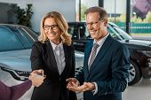 Partial View Of Female Car Dealer Giving Car Key To Smiling Couple In Formal Wear In Dealership Salo poster