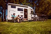 Woman with a man resting near motorhomes in nature. Family vacation travel, holiday trip in motorhom poster