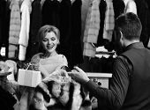Shop Assistant With Beard And Mustache Shows Fur Coat To Lady. Girl In Pink Fur Coat Looks At Stripe poster