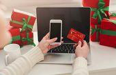 Christmas Online Shopping. Female Makes Order On Blank Smartphone With Credit Card, Sitting At Lapto poster