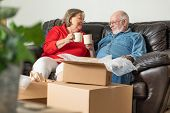 Tired Senior Adult Couple Resting on Couch with Cups of Coffee Surrounded with Moving Boxes. poster