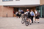 Group Of High School Students Wearing Uniform Arriving At School Walking Or Riding Bikes Being Greet poster